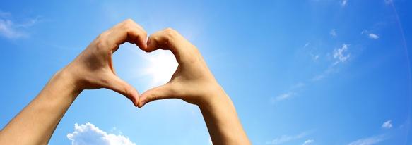 Handsilhouette in Form eines Herzens am Himmel